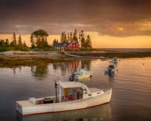 red house beside body of water with white motor boats during daytime