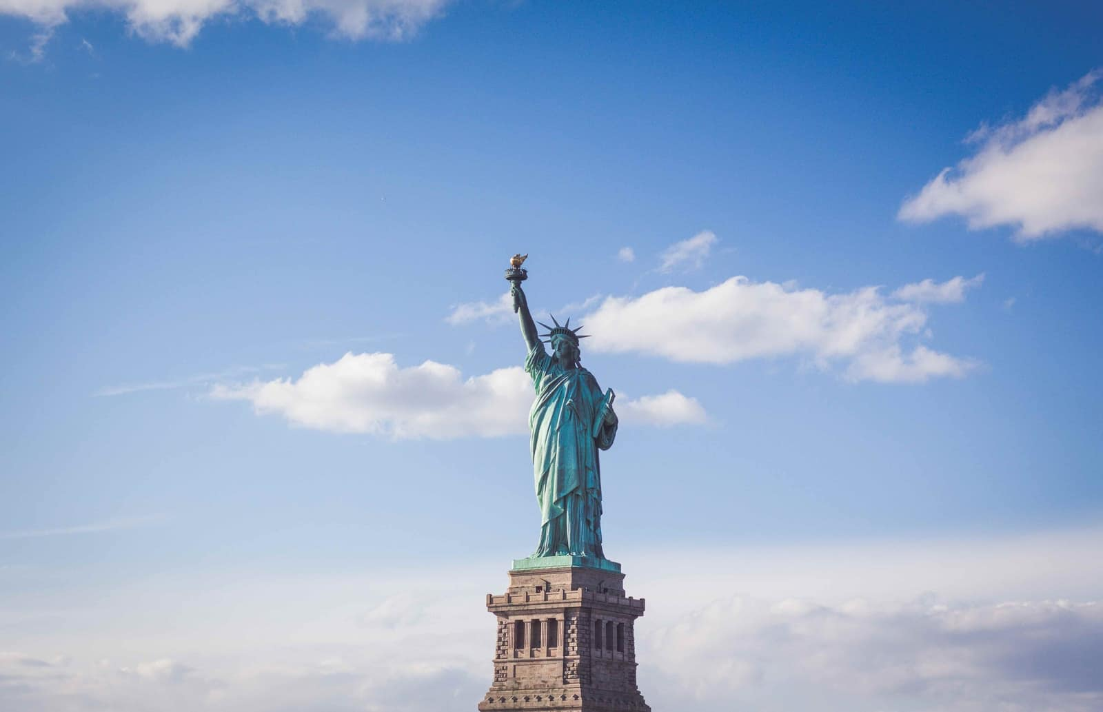Statue of Liberty, New York under white and blue cloudy skies